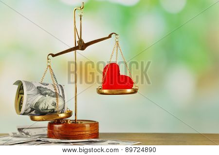 Money and heart in balance scales on light blurred background