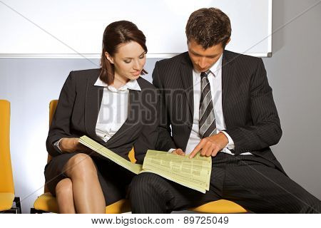 Businessman and businesswoman reading newspaper at waiting room