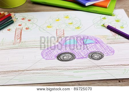 Kids drawing on white sheet of paper with crayon,closeup