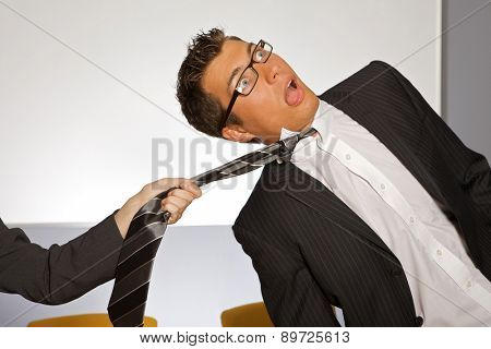 Businesswoman pulling businessman by tie