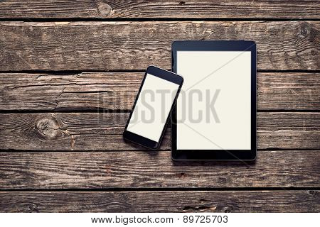 Tablet and smartphone on old wood desktop. Clipping paths included.