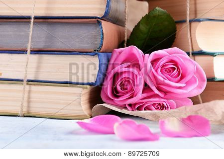 Beautiful pink roses with stack of books, closeup