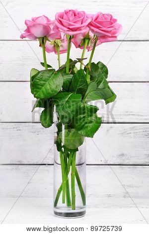 Beautiful pink roses on wooden background