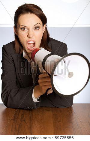 Portrait of businesswoman shouting through megaphone