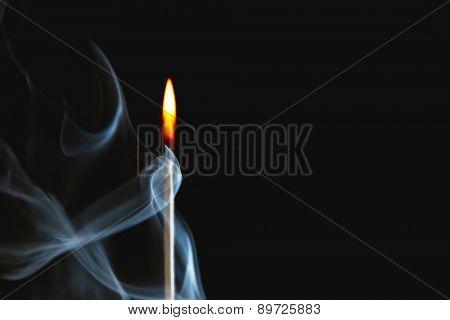 Burning match in smoke on dark background