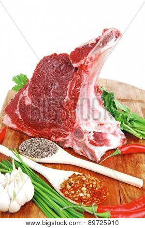 butchery : fresh raw beef lamb big rib ready to cooking with green stuff on wooden plate isolated over white background
