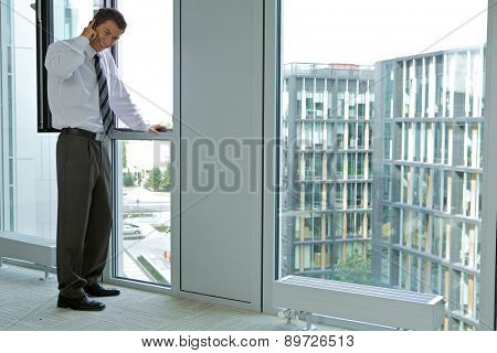 Young businessman looking thru window
