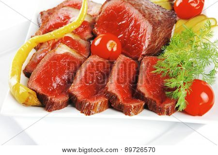 grilled beef meat entrecote on white plates with peppers and tomato isolated on white background