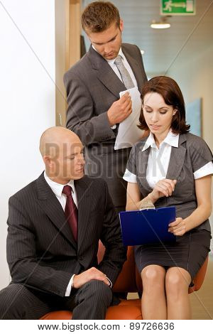 Young confident boss and his secretary looking on documents