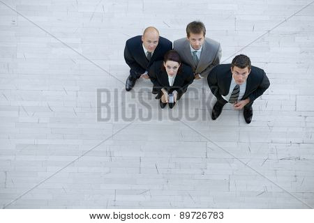 Businesswoman and men looking up