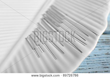 Acupuncture needles on plate on wooden table, closeup