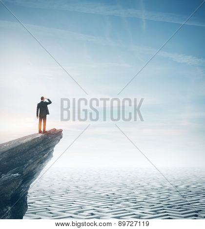 Businessman standing on a rock and looking at huge maze. 3d rendering