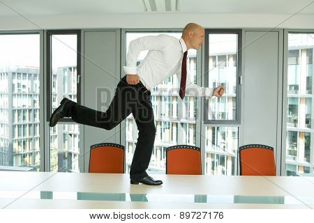 young confident caucasian businessman running on the office table