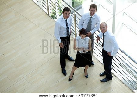 Businessmen and woman standing by railing, portrait