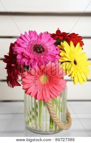 Colorful gerbera in glass vase on table, closeup