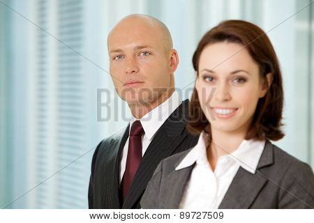 Portrait of young caucasian businessman and businesswoman in office