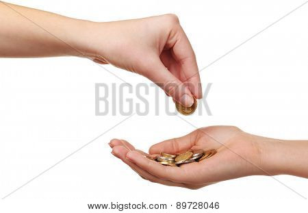 Female hand putting coin into another hand isolated on white