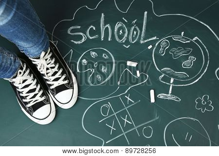 Female feet on blackboard background with inscriptions and sketches
