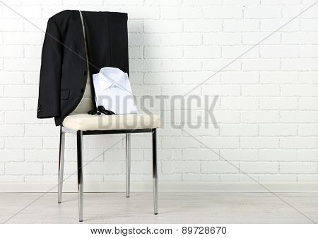 School clothes for boy on chair, on white wall background