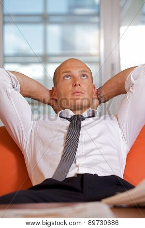Businessman with hands behind head