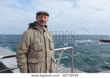 Senior man on the pier against the sea in a springtime day