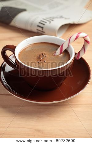 Cup of coffee with candy cane and a newspaper on a table