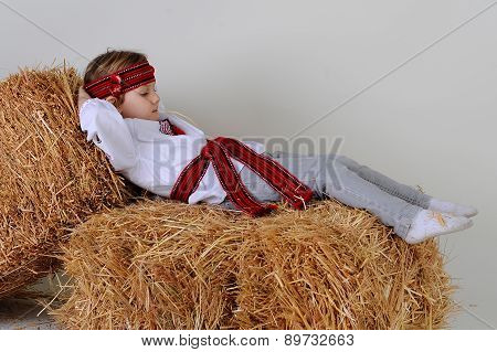 Ukrainian Girl In National Dress Lying On Hay