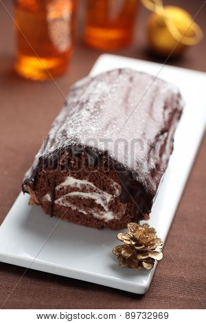 Yule log cake topped with chocolate on a Christmas table