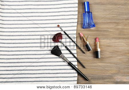 Striped T-shirt and various cosmetics on wooden background