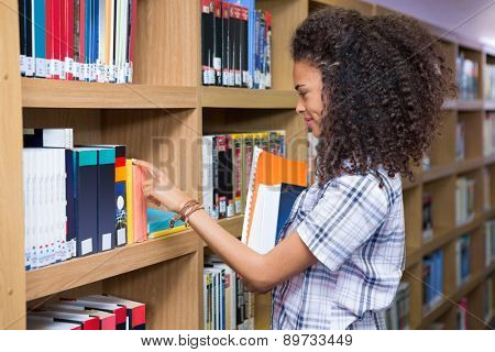 Student picking a book from shelf in library at the university