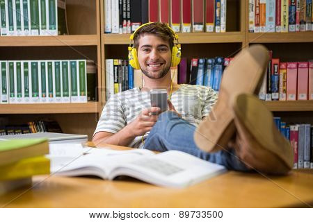 Student listening music in the library with smartphone at the university