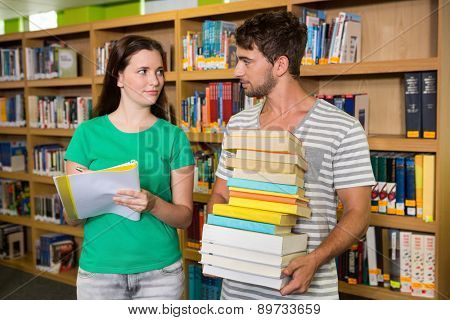 Students with pile of books in the library at the university