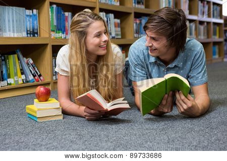 Students reading book lying on library floor at the university