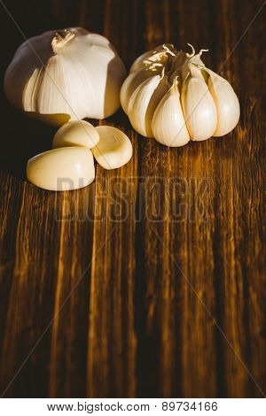 Garlic cloves and bulb on chopping board with copy space