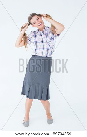 Geeky hipster holding her pigtails on white background