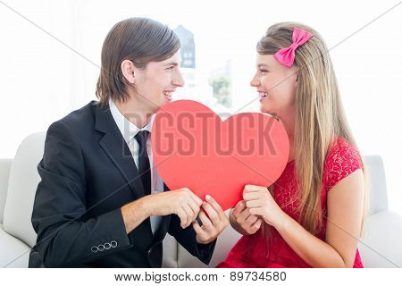 Cute geeky couple smiling and holding heart on the couch