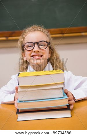 Smiling pupil holding books at elementary school