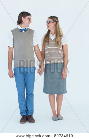 Geeky hipster couple holding hands and looking at each other on white background