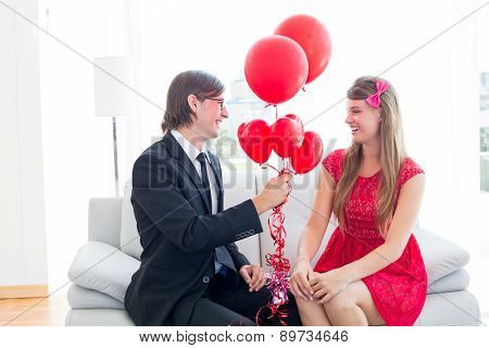 Cute geeky couple with red balloons on the couch