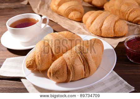 Delicious croissants on plate on table close-up
