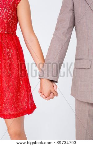 Hipster couple standing hand in hand on white background