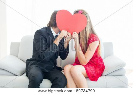 Cute geeky couple kissing and holding heart over faces on the couch