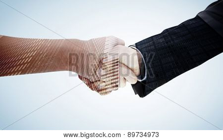 Close up of a handshake against low angle view of skyscrapers