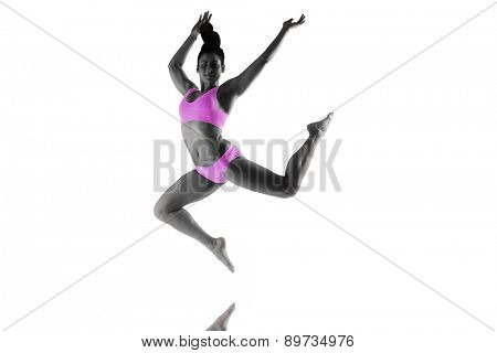 Fit brunette jumping and posing against mirror