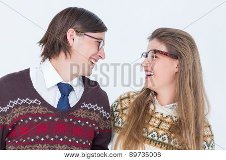 Happy geeky hipster couple looking at each other on white background