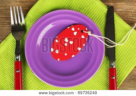 Blank tag on color plate and napkin on wooden table, closeup