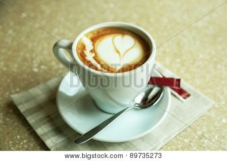 Cup of cappuccino with heart on foam on table in cafe