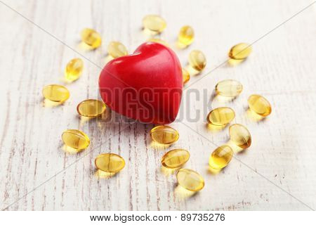 Red heart and cod liver oil, on wooden background