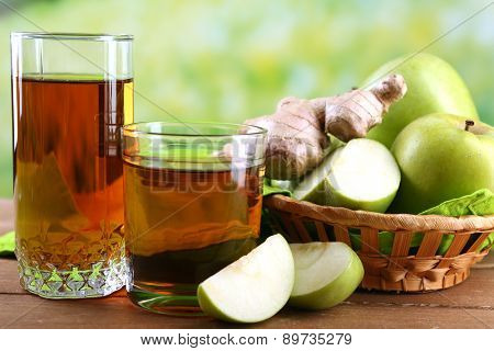 Glass of healthy fresh juice of apples and ginger on wooden background