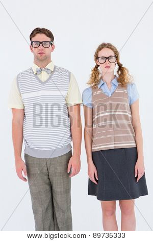 Geeky hipster couple looking at camera on white background